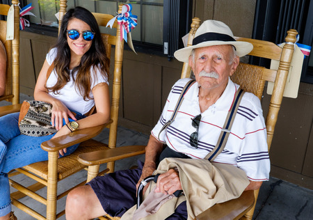 octogenarian: Elderly eighty plus year old grandfather sitting on a rocking chair with his granddaughter.
