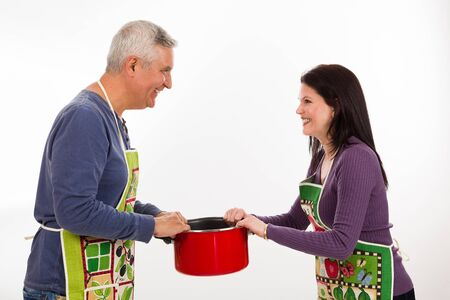 middle age couple: Attractive middle age couple wearing aprons and holding a pot with a funny expression on a white background.