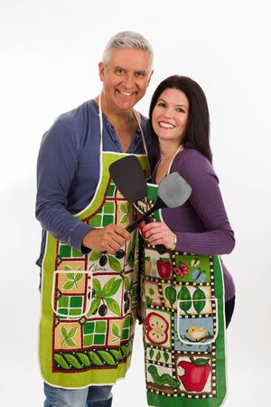 middle age: Attractive middle age couple wearing aprons and holding spatulas on a white background.
