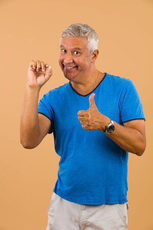 unshaven: Handsome unshaven middle age man studio portrait with a beige background holding a blue pill. Stock Photo