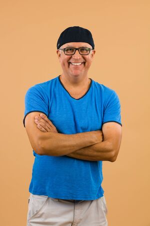 hombre con sombrero: Apuesto sin afeitar mediana edad retrato de hombre de estudio con un fondo de color beige. Foto de archivo