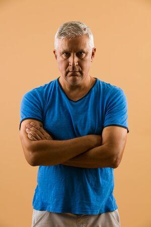 unshaven: Handsome unshaven middle age man studio portrait with a beige background. Stock Photo