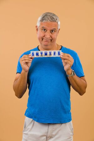 middle age man: Handsome unshaven middle age man studio portrait with a beige background holding a vitamin pill box.