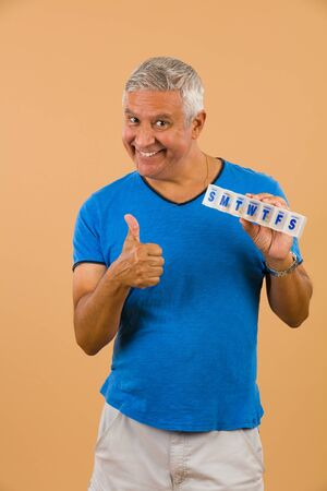 unshaven: Handsome unshaven middle age man studio portrait with a beige background holding a vitamin pill box.