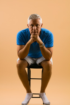 middle age man: Handsome unshaven middle age man studio portrait with a beige background. Stock Photo