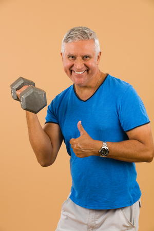 unshaven: Handsome unshaven middle age man studio portrait with a beige background holding a barbell.