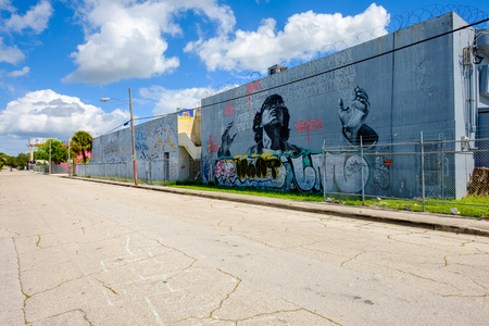 Miami, Florida USA - October 4, 2015: The  urban Wynwood area in midtown has become a popular tourist destination to view the colorful graffiti art murals that cover the facades of commercial warehouse style buildings.