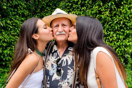 Ouderen tachtig plus-jarige man wordt gekust door zijn kleindochters in een buitenomgeving. Stockfoto