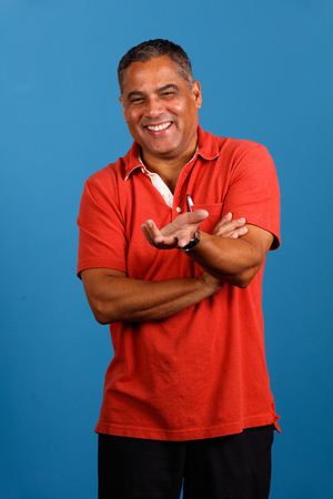 spanish looking: Handsome middle age hispanic man portrait with a blue background.