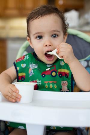 Bebé hambriento alimentarse postre en un ambiente de hogar.