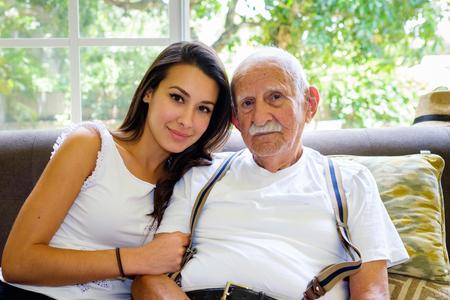 Ältere achtzig zzgl Jahre alter Mann mit Enkelin in einem Heim Einstellung. Standard-Bild