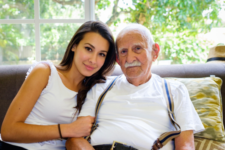 elderly adults: Elderly eighty plus year old man with granddaughter in a home setting.