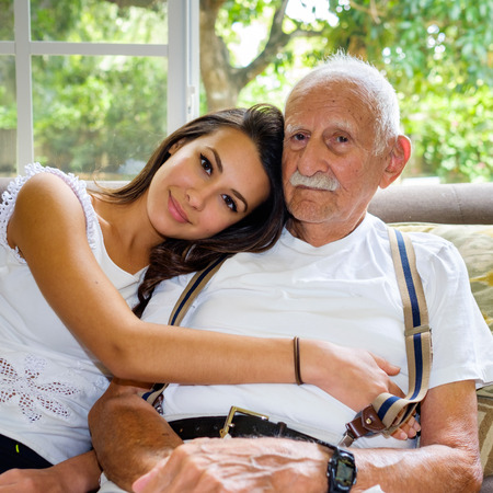 happy families: Elderly eighty plus year old man with granddaughter in a home setting.