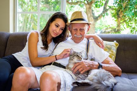 Ancianos hombre de ochenta años con nieta y gato en un hogar.
