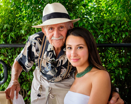 eighty: Elderly eighty plus year old man with granddaughter in a outdoor setting.
