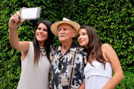 高齢者 80 プラス屋外の設定で、selfie を取って彼の孫娘を持つ歳の男性。