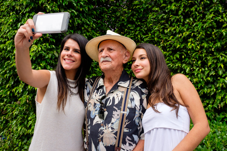 granddaughters: Elderly eighty plus year old man with his granddaughters taking a selfie in a outdoor setting.