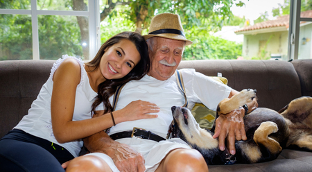 animal family: Elderly eighty plus year old man with granddaughter in a home setting.