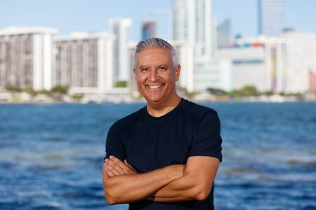 middle adult: Handsome middle age man outdoor portrait with a downtown bay skyline background. Stock Photo