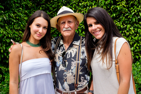 granddaughters: Elderly eighty plus year old man with his granddaughters in a outdoor setting. Stock Photo
