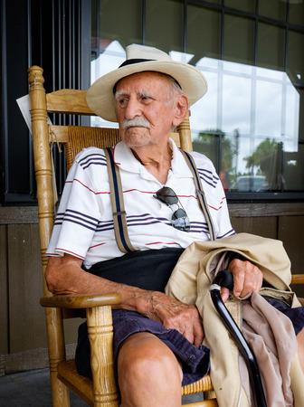 rocking chair: Elderly eighty plus year old man sitting on a rocking chair.
