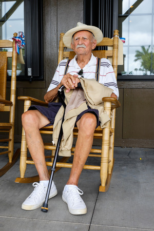 cane chair: Elderly eighty plus year old man sitting on a rocking chair.