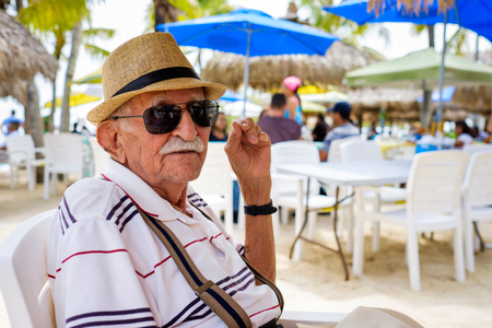 octogenarian: Elderly eighty plus year old man wearing a hat in a outdoor restaurant setting.