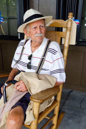 old man sitting: Elderly eighty plus year old man sitting on a rocking chair.