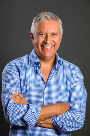 blue shirt: Handsome middle age man studio portrait on a gray background.