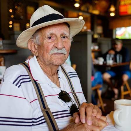 aging american: Elderly eighty plus year old man wearing a hat in a restaurant setting.