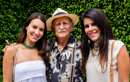 Elderly eighty plus year old man with his granddaughters in a outdoor setting. Stockfoto