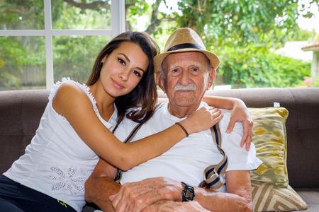 Ouderen tachtig plus jaar oude man met kleindochter in een thuissituatie. Stockfoto