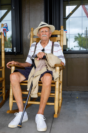 persons: Elderly eighty plus year old man sitting on a rocking chair.