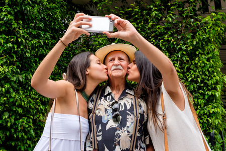 young beautiful woman: Elderly eighty plus year old man with his granddaughters taking a selfie in a outdoor setting.