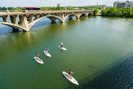 boarders: Austin, TX USA - April 14: Skyline view of the downtown area along the Colorado River with paddle boarders cruising by. Editorial