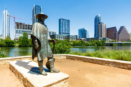 lady bird: Austin, TX USA - April 14, 2016: Skyline view of the downtown district along the Colorado River with the statue of the late Stevie Ray Vaughan. Editorial