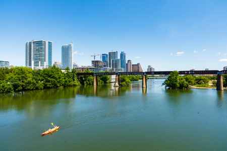 destination scenics: Austin, TX USA - April 14: Skyline view of the downtown area along the Colorado River with kayakers cruising by.