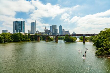 colorado river: Austin, TX USA - April 14: Skyline view of the downtown area along the Colorado River with paddle boarders cruising by. Editorial