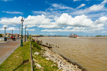 mississippi river: New Orleans, LA USA - April 20, 2016: The Mississippi River with departing paddle boat viewed from the French quarter.