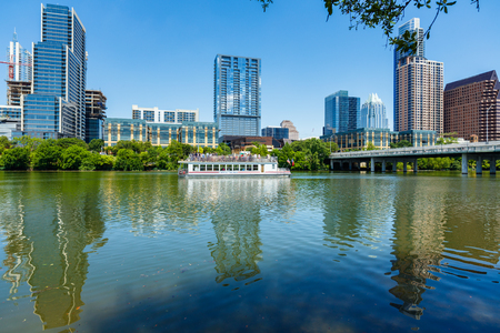 tx: Austin, TX USA - April 14, 2016: Skyline view of  the downtown district along the Colorado River with a tour boat cruising by.