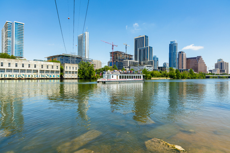 capital of colorado: Austin, TX USA - April 14, 2016: Skyline view of  the downtown district along the Colorado River with a tour boat cruising by.