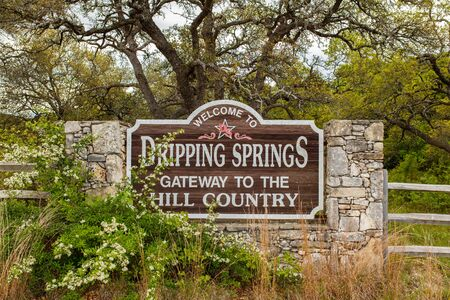 small country town: Dripping Springs, Texas USA - April 6, 2016: Welcome to Dripping Springs sign from this small town in the Texas Hill Country.