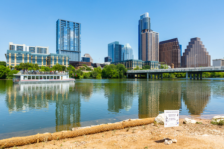 colorado skyline: Austin, TX USA - April 14, 2016: Skyline view of  the downtown district along the Colorado River with a tour boat cruising by.