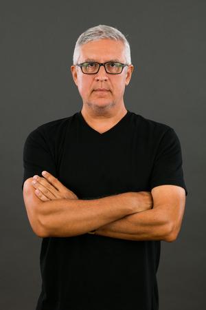 v neck: Handsome unshaven middle age man studio portrait with a gray background.