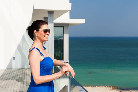 sex appeal: Beautiful middle age woman enjoying the sights of Miami Beach from a balcony.