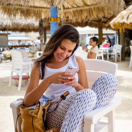 restaurant setting: Beautiful young woman enjoying the outdoors in a tiki style restaurant setting in the Florida Keys.