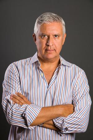 studio portrait: Handsome middle age man studio portrait on a gray background.