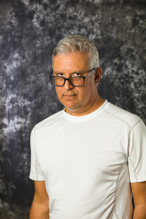 middle age man: Handsome unshaven middle age man studio portrait with a gray background.