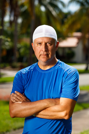 middle age man: Handsome unshaven middle age man outdoor portrait wearing a white cap. Stock Photo