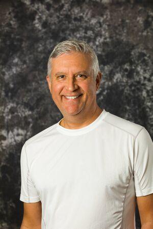 unshaven: Handsome unshaven middle age man studio portrait with a gray background.